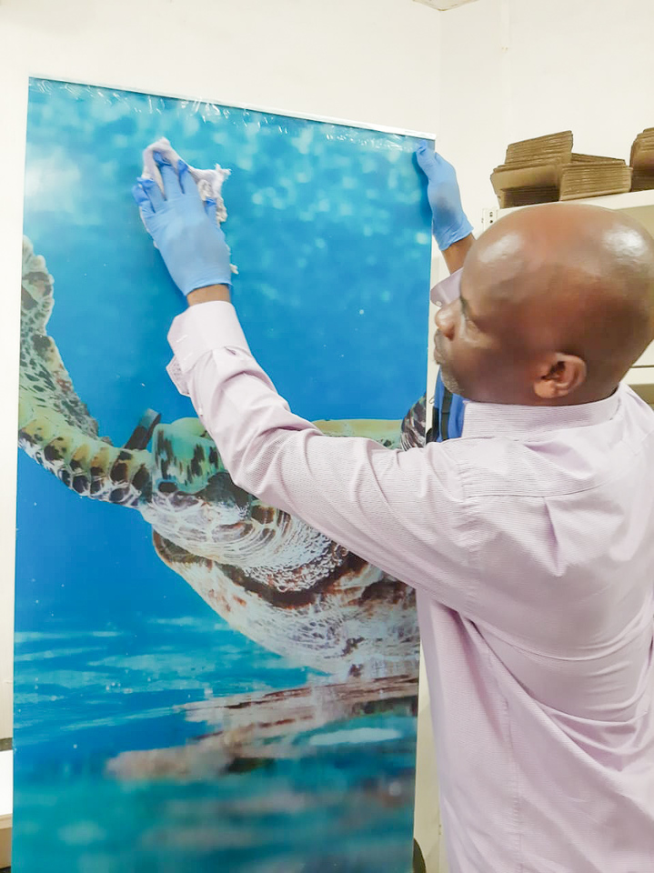 PrintWild worker wiping an Acrylic Print with sanitizer